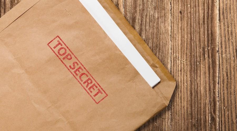 bigstock-Open-Top-Secret-Envelope-On-Ta-8130397